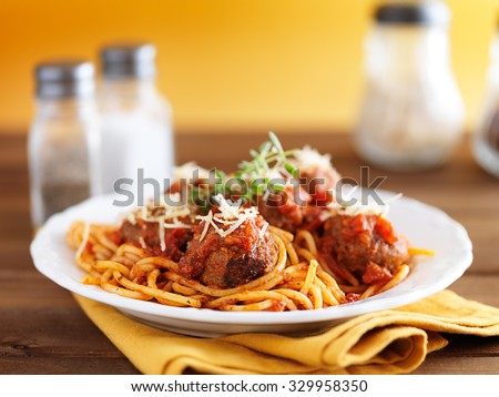 spaghetti and meatballs on rustic wooden table with yellow background - stock photo