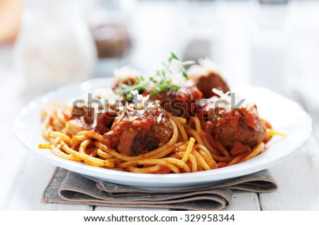 spaghetti and meatballs with oregano garnish on rustic table shot with selective focus - stock photo