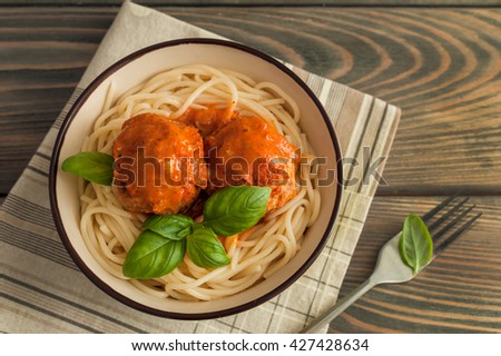spaghetti and meatballs with tomato sauce on wooden background - stock photo