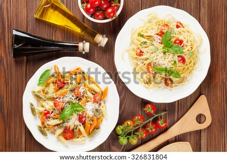 Spaghetti and penne pasta with tomatoes and basil on wooden table. Top view
