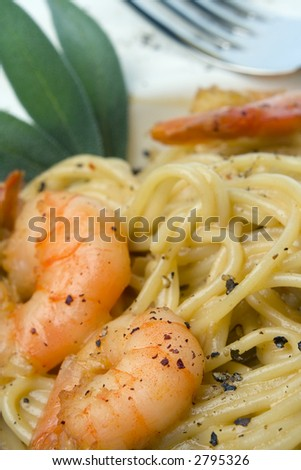 Spaghetti and prawns in cream sauce, herb garnish. Served on deep white, round bowl with wide rim sprinkled with ground pepper. Portrait, extreme macro, selective focus, shallow depth of field.