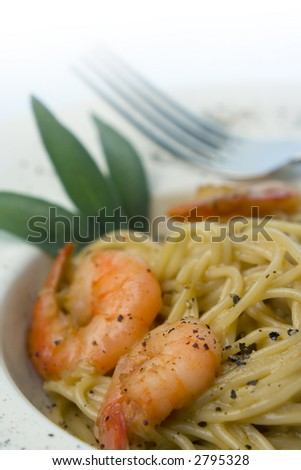 Spaghetti and prawns in cream sauce, herb garnish. Served on deep white, round bowl with wide rim sprinkled with ground pepper. Portrait, macro, shallow depth of field, fade to white background.