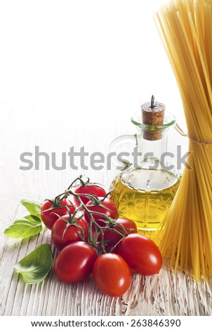 Spaghetti and tomatoes with basil on a vintage wooden table - stock photo