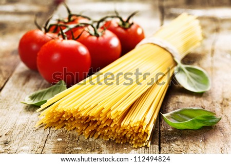 Spaghetti and tomatoes with herbs on an old and vintage wooden table - stock photo