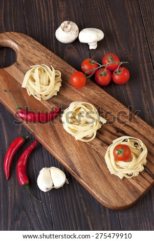 Spaghetti and tomatoes with herbs on  old and vintage wooden board - stock photo
