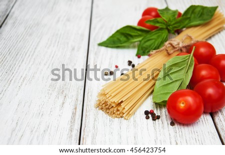 spaghetti, basil and tomatoes on a old wooden background