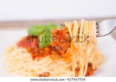 Spaghetti bolognese decorated with basil being eaten with a fork - stock photo