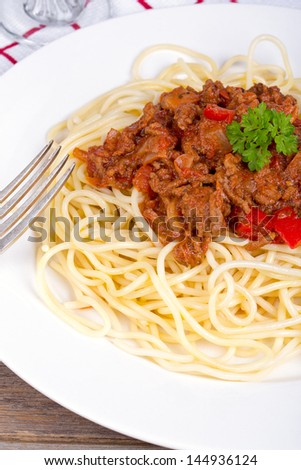 Spaghetti bolognese dinner on red and white checkered tablecloth, with the stem of a wine glass just showing in the background
