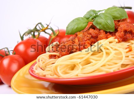 Spaghetti bolognese on a plate decorated with basil and some fresh tomatoes