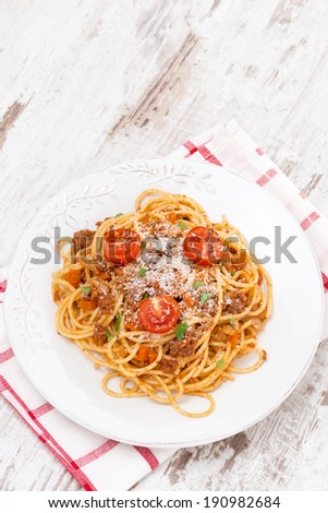 spaghetti bolognese on a white plate, top view, vertical - stock photo