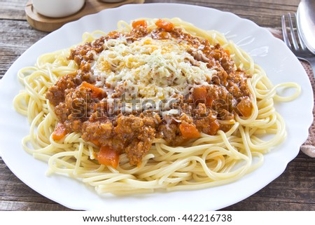 Spaghetti bolognese on plate with fork and spoon - stock photo