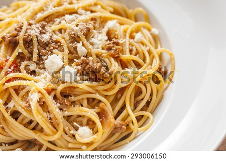 Spaghetti Bolognese, topped with Parmesan cheese, in a white bowl - stock photo