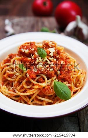 spaghetti bolognese with basil and parmesan cheese on old rustic wooden planks - stock photo