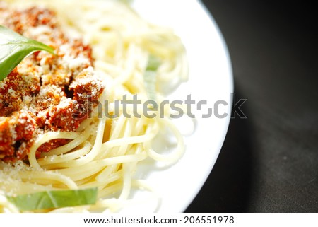 Spaghetti bolognese with basil in white plate on black table - stock photo