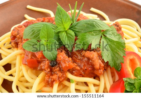 Spaghetti Bolognese with fresh herb spices - oregano, basil, rosemary, celery and red pepper, served on rustic, brown ceramic plate over white background
