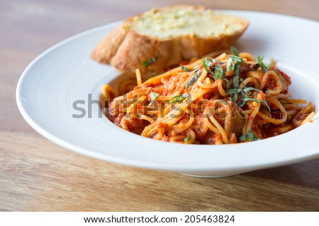 spaghetti bolognese with garlic bread wooden table - stock photo