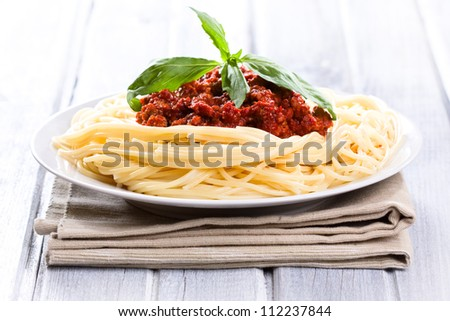 Spaghetti bolognese with green basil - stock photo