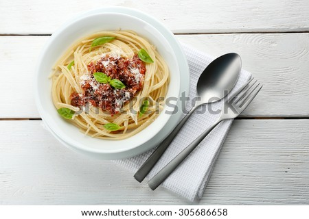 Spaghetti Bolognese with parmesan cheese in white bowl, on color wooden background - stock photo