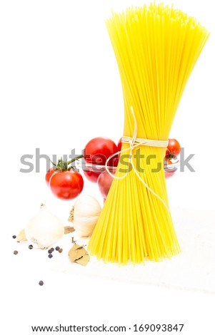 spaghetti, cherry tomatoes, onions, garlic, bay leaf, pepper on a white background