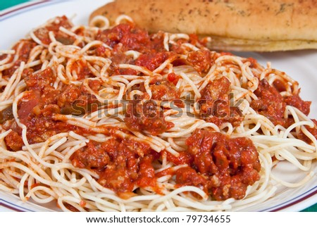Spaghetti dinner with meat sauce and bread-stick on a plate. - stock photo
