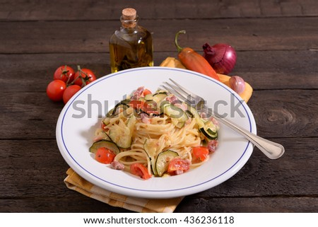 Spaghetti dish with zucchini bacon and tomato flavored with sage oil on wooden table - stock photo
