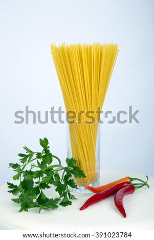 Spaghetti  in a glass near vegetables ,dill ,white background , yellow  ,green leaves ,radish,fresh vegetables, red  ,green, tasty ,spring ,organic food ,eco ,yellow, italian