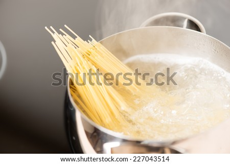 Spaghetti in pan cooking in boiling water - stock photo