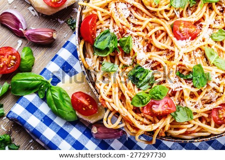 Spaghetti. Italian and Mediterranean cuisine. Spaghetti bolognese with cherry tomato and basil. Spaghetti with tomato sauce on blue checkered tablecloth and rustic wooden table.  - stock photo