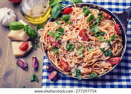 Spaghetti. Italian and Mediterranean cuisine.  Spaghetti bolognese with cherry tomato and basil. Spaghetti with tomato sauce on blue checkered tablecloth and rustic wooden table - stock photo