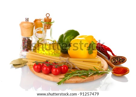 spaghetti, jar of oil, spices and vegetables on wooden board isolated on white - stock photo
