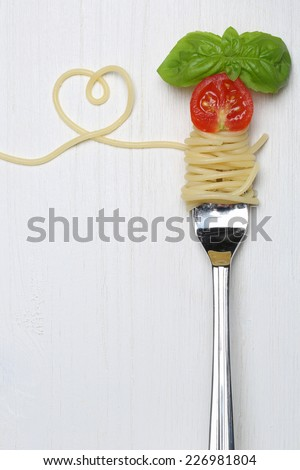 Spaghetti noodles pasta meal with heart, tomato and copy space on a fork - stock photo