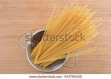 spaghetti noodles uncooked in strainer on wooden counter
