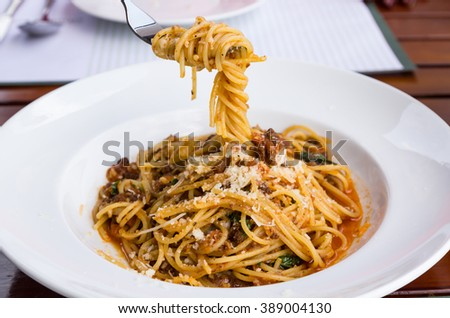 Spaghetti noodles with meat sauce on white plate.