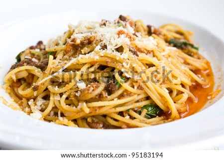 Spaghetti noodles with meat sauce on white plate