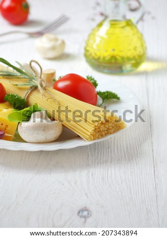 Spaghetti, olive oil, vegetables and herbs on an old wooden table. Italian cuisine. - stock photo