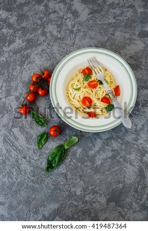 Spaghetti pasta with cherry tomatoes, basil and parmesan cheese, top view, copy space - stock photo