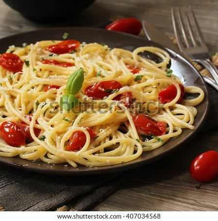 Spaghetti pasta with cherry tomatoes garnished with basil leaf, selective focus