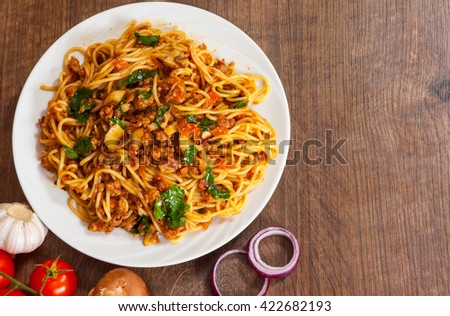 spaghetti pasta with mushroom, vegetables and minced meat in a plate on wooden table