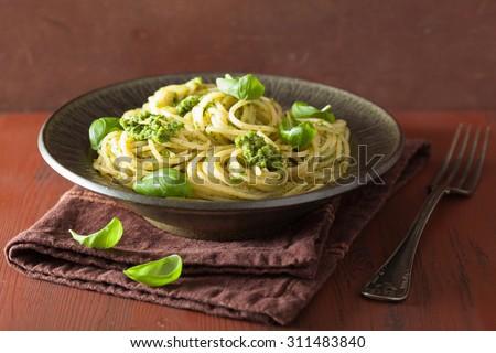 spaghetti pasta with pesto sauce over rustic table - stock photo