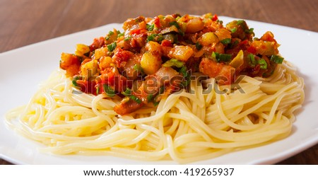 Spaghetti pasta with vegetables mix and bacon on white plate