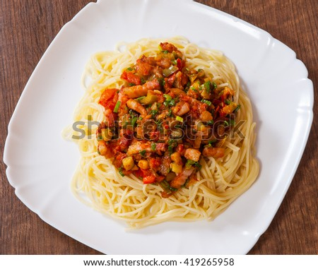 Spaghetti pasta with vegetables mix and bacon on white plate - stock photo