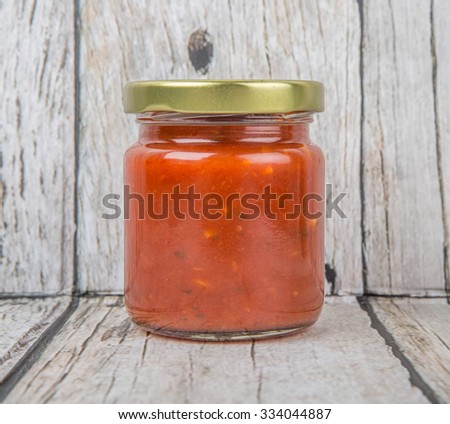 Spaghetti sauce in a mason jar over wooden background