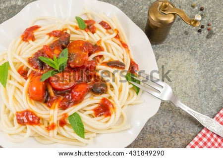 Spaghetti served with ketchup, cheese, vegetables and parsley.