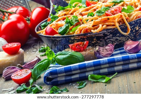 Spaghetti. Spaghetti bolognese with cherry tomato and basil. Spaghetti with tomato sauce on blue checkered tablecloth and rustic wooden table - stock photo