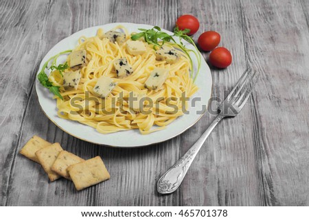 Spaghetti tagliolini with blue cheese, cherry tomatoes, lettuce, crackers, light white wooden background