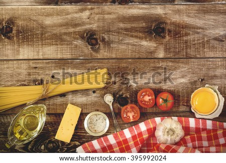 Spaghetti, tomatoes and cheese on a wooden background . Pasta Ingredients.  Top view - stock photo