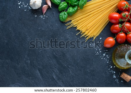 Spaghetti, tomatoes and others ingrdients for italian pasta on blackboard - stock photo