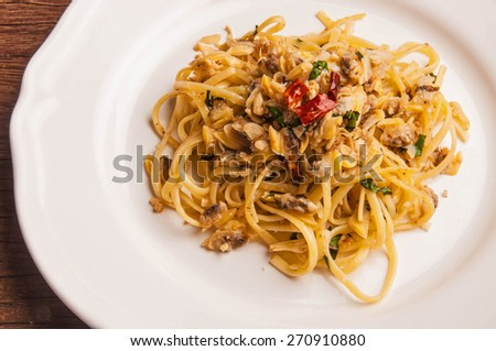 Spaghetti Vongole Fresh Clams with Chilli and Garlic, in vintage white plate, on wood table background, rustic still life style. - stock photo