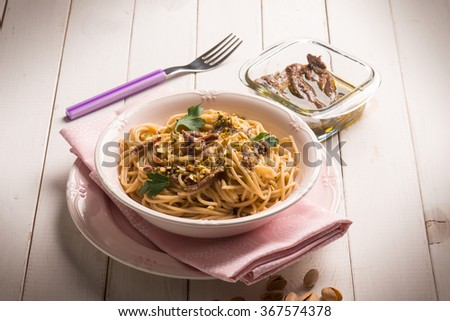 spaghetti with anchovies and pistachio nuts - stock photo