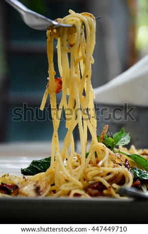 spaghetti with bacon and dried chilli on fork